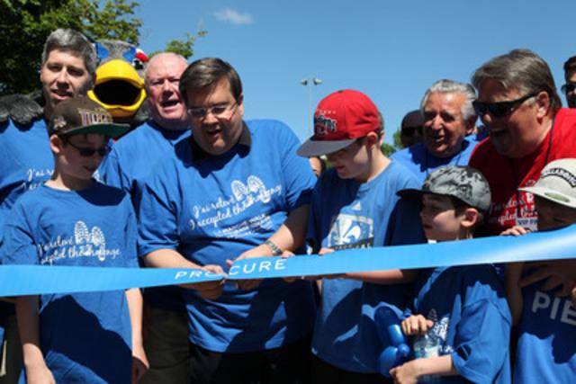 Le maire de Montréal Denis Coderre coupe le ruban bleu avant de se joindre à des centaines de montréalais pour la Marche du Courage PROCURE 2014 au Parc Jean-Drapeau afin de soutenir la lutte contre le cancer de la prostate (Groupe CNW/PROCURE)